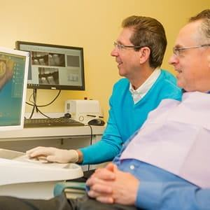 Dr. Silberman, a dentist in Waldorf MD, talking to a patient about his CEREC machine.